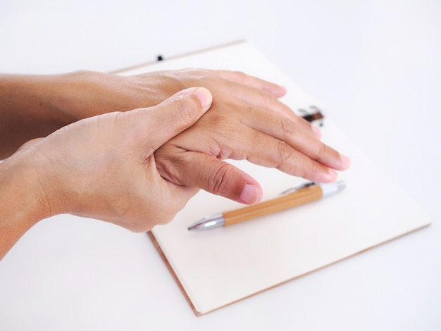 Молодая азиатская работница, страдающая от боли в руке, спускового пальца и массажа на болезненном запястье медицинский симптом и концепция здравоохранения.