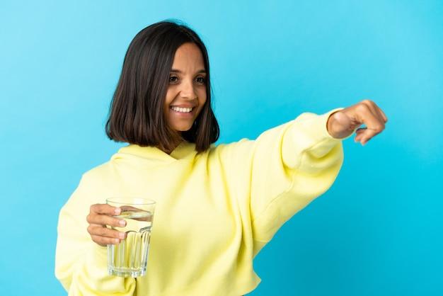 親指を立てるジェスチャーを与える青い背景に分離された水のガラスを持つ若いアジアの女性