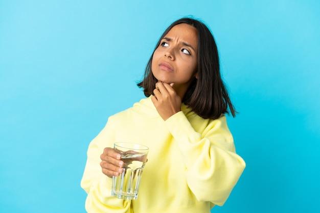 疑いを持っている青い背景に分離された水のガラスを持つ若いアジアの女性