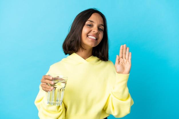 幸せな表情で手で敬礼青い背景に分離された水のガラスを持つ若いアジアの女性