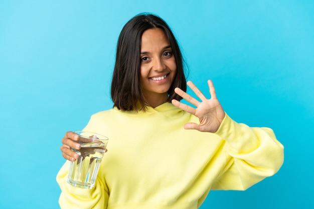 指で5を数える青で分離された水のガラスを持つ若いアジアの女性