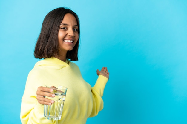 来るように誘うために横に手を伸ばして青い上に隔離された水のガラスを持つ若いアジアの女性