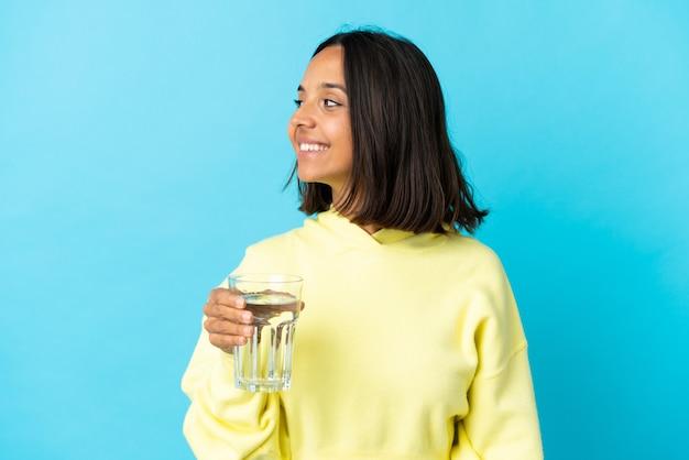 파란색 찾고 측면에 절연 물 한 잔을 가진 젊은 아시아 여자