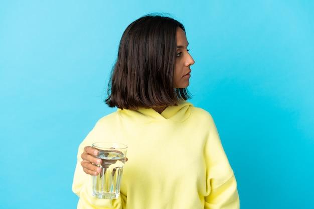 측면을 찾고 파란색에 고립 된 물 한 잔을 가진 젊은 아시아 여자