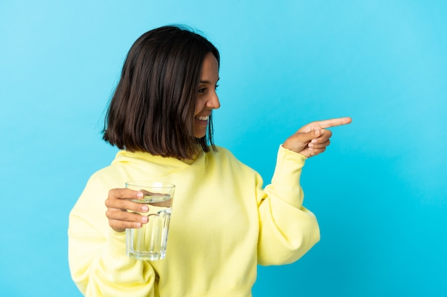 横に青い人差し指で隔離され、製品を提示する水のガラスを持つ若いアジアの女性
