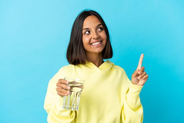 좋은 아이디어를 가리키는 파란색에 고립 된 물 한 잔과 젊은 아시아 여자