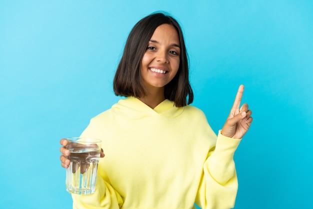 파란색 표시 및 최고의 기호에 손가락을 들어 올려 절연 물 한 잔을 가진 젊은 아시아 여자