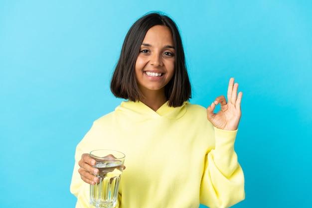 指でokサインを示す青に分離された水のガラスを持つ若いアジアの女性