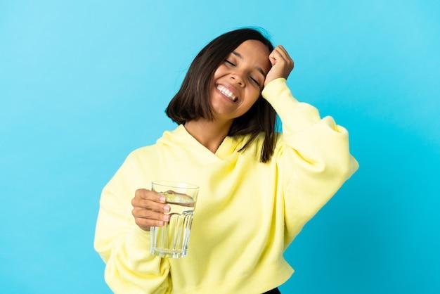 물 한 잔을 가진 젊은 아시아 여자는 많이 웃고 파란색 벽에 절연