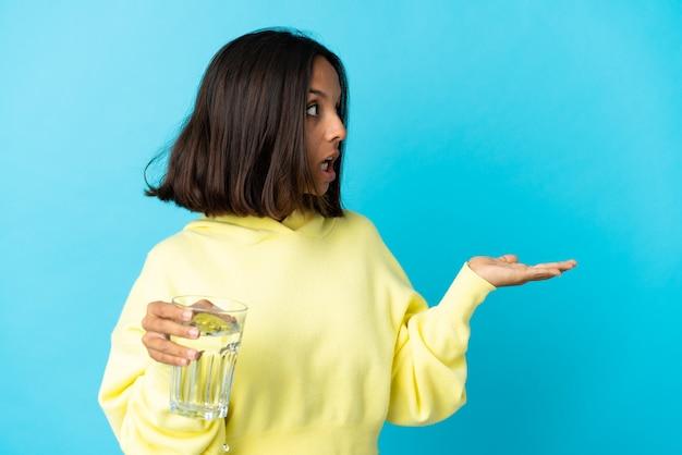 측면을 찾고있는 동안 놀라운 표정으로 파란색 벽에 절연 물 한 잔을 가진 젊은 아시아 여자