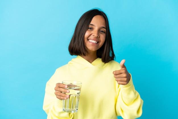 Молодая азиатская женщина со стаканом воды изолирована на синей стене с большими пальцами руки вверх, потому что произошло что-то хорошее