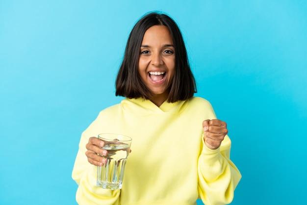 勝者の位置での勝利を祝う青に水のガラスを持つ若いアジアの女性
