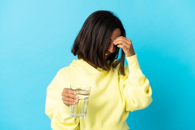 青い笑いに水のガラスを持つ若いアジアの女性