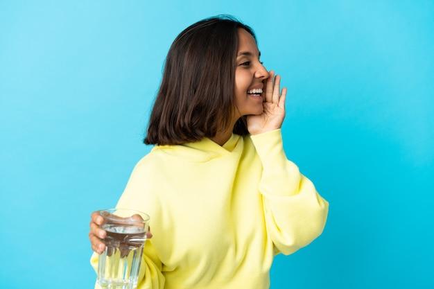 横に大きく開いた口で青い叫びに水のガラスを持つ若いアジアの女性