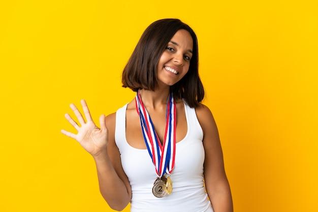 Молодая азиатская женщина с медалями, изолированными на белом фоне, считая пять пальцами
