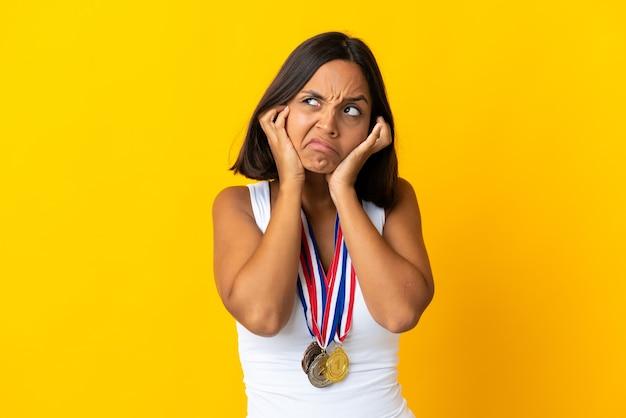 Молодая азиатская женщина с медалями на белом фоне разочарована и закрывает уши
