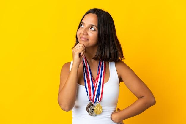 Молодая азиатская женщина с медалями, изолированными на белом фоне, сомневается