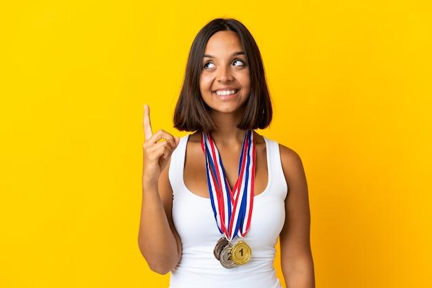 Молодая азиатская женщина с медалями, изолированными на белом фоне, указывая на отличную идею
