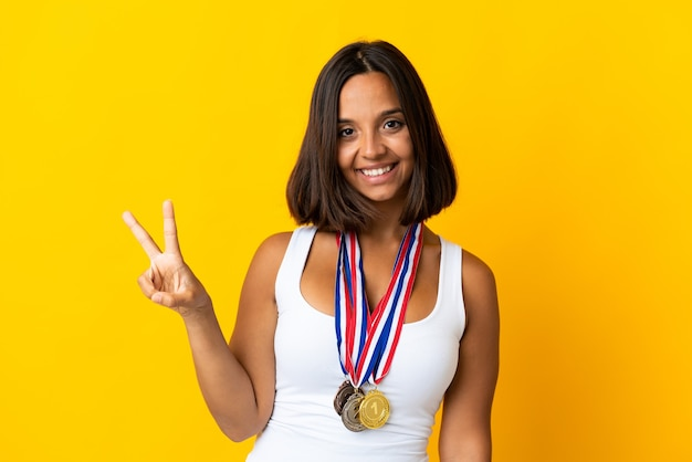 Молодая азиатская женщина с медалями, изолированные на белом фоне, улыбается и показывает знак победы