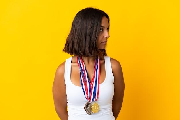 Молодая азиатская женщина с медалями, изолированными на белом, глядя в сторону