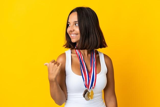 Молодая азиатская женщина с медалями, изолированными на белом, указывая в сторону, чтобы представить продукт