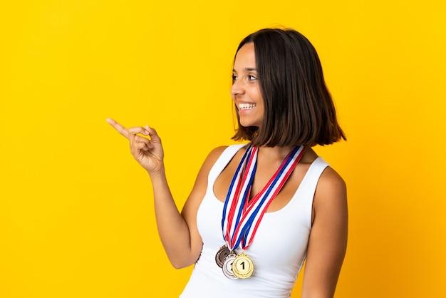 Молодая азиатская женщина с медалями, изолированными на белой стене, указывая пальцем в сторону и представляя продукт
