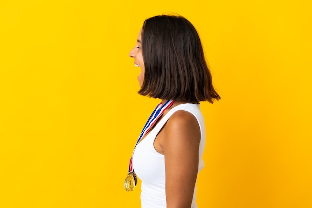 Young asiatic woman with medals isolated on white background laughing in lateral position