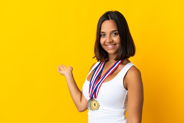 Young asiatic woman with medals isolated on white extending hands to the side for inviting to come