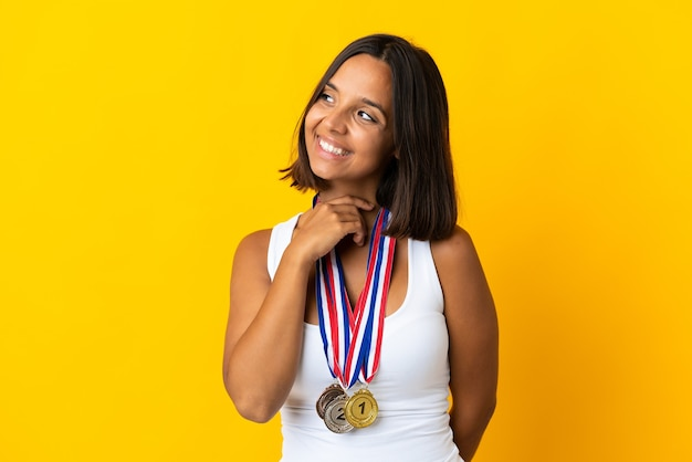 Young asiatic woman with medals isolated on white looking up while smiling