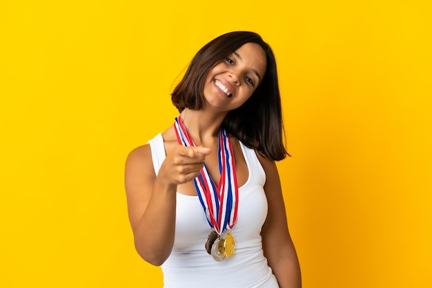 Young asiatic woman with medals isolated on white wall pointing front with happy expression
