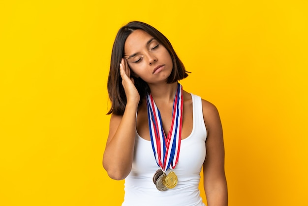 Young asiatic woman with medals isolated on white with headache