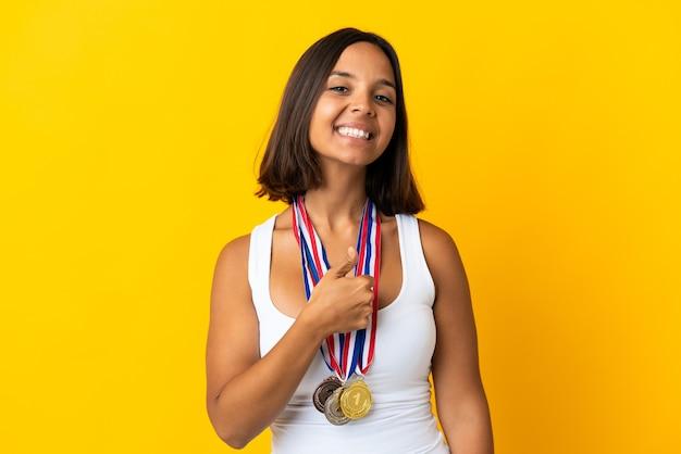 Молодая азиатская женщина с медалями на белом показывает палец вверх