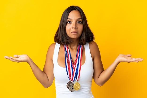 Молодая азиатская женщина с медалями на белом сомневается, поднимая руки
