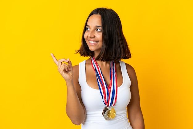 Молодая азиатская женщина с медалями на белом, намереваясь реализовать решение, подняв палец вверх