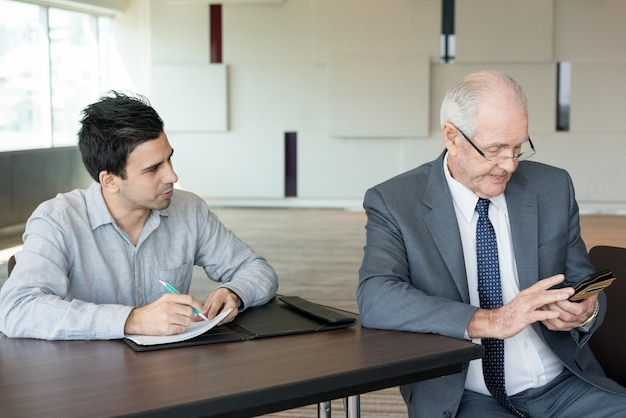 Young assistant writing tasks at meeting with boss