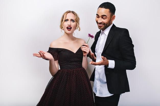 若い黒人の豪華なイブニングドレスのブロンドの女性は彼女の後ろに笑みを浮かべてタキシードでハンサムな男からの花の贈り物に不満を探しています。バレンタインデー、プレゼント、楽しんで。