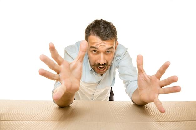 Giovane uomo stupito che apre il più grande pacchetto postale isolato su bianco. modello maschio scioccato sopra una scatola di cartone che guarda dentro.