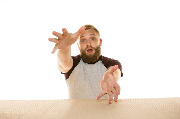 Giovane uomo stupito che apre il più grande pacchetto postale isolato su bianco. modello maschile scioccato sopra una scatola di cartone