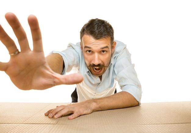 Giovane uomo stupito che apre il più grande pacco postale isolato sul muro bianco