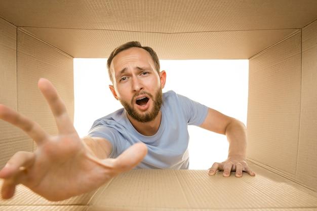Giovane uomo stupito che apre il pacco postale più grande