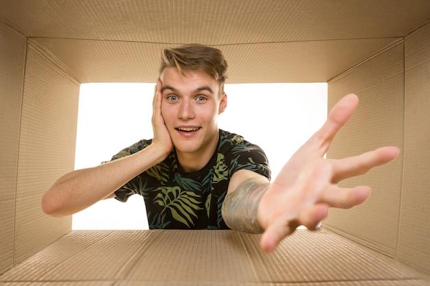 白で隔離された最大の郵便パッケージを開いている若い驚いた男。段ボール箱の上に幸せな男性モデル