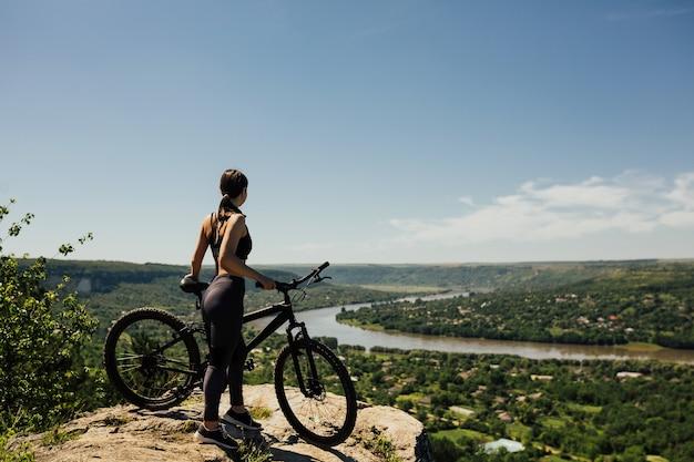 川と町の景色を眺めながら丘の上にマウンテンバイクで若いアスリートバイカー