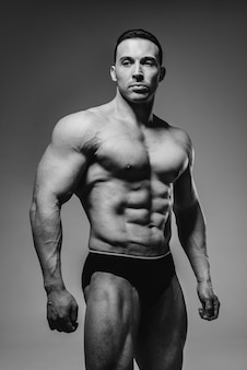 A young athlete bodybuilder poses in the studio topless, showing off his abs and muscles. black and white.