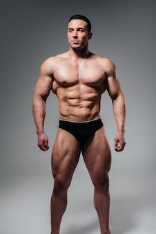 A young athlete bodybuilder poses in the studio topless, showing off his abs and muscles. sport.