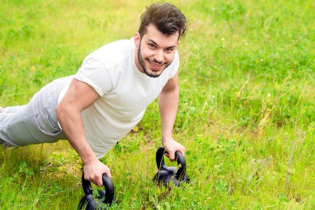 Молодой спортсмен делает отжимания на зеленой лужайке дома, концепция простого и здорового образа жизни