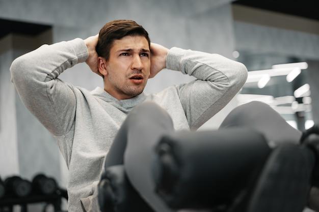 현대 체육관에서 복근 운동을 하는 젊은 운동선수