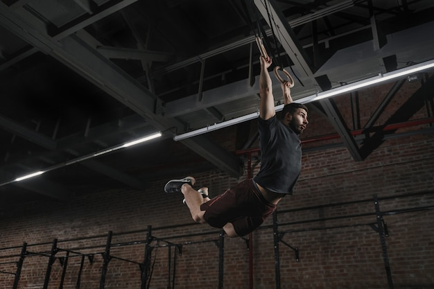 クロスフィットジムで体操リングの懸垂をしている若いアスリート。筋肉のアップを練習しているハンサムな男は、トレーニング運動をスイングします。