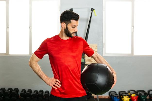ボールを持ってジムで運動する若いアスリート
