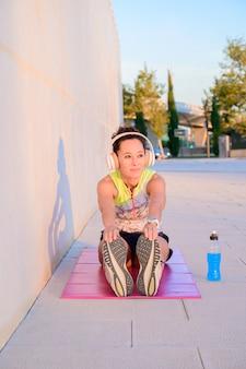 Девушка молодой спортсмен выполняет растяжку и расслабляется после тренировки