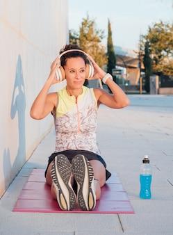Девушка молодой спортсмен надевает шлемы, чтобы расслабиться во время упражнений